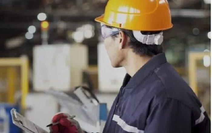 trabalhador de capacete laranja e macacão azul marinho