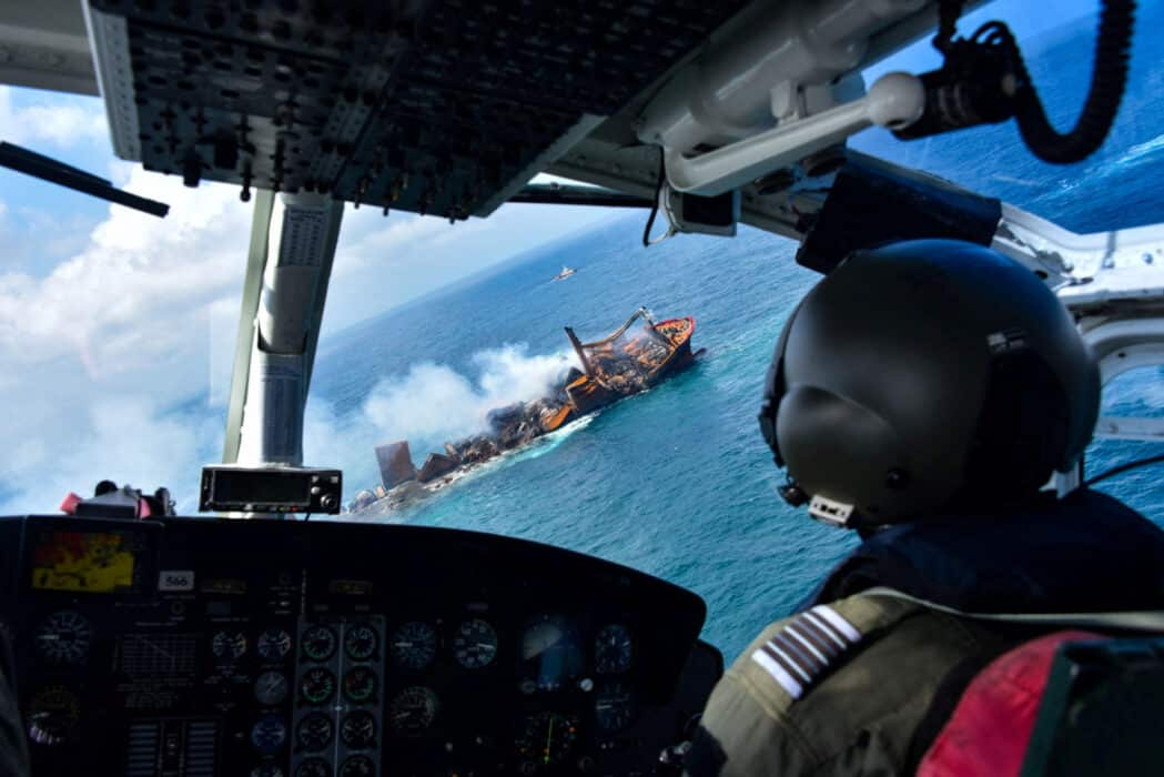 Helicoptero sobrevoando navio na costa do Sri Lanka prestes a afundar